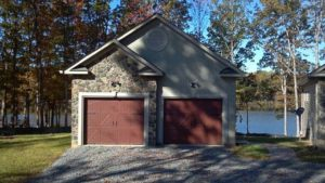 Separate garage with red door next to the lake
