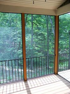 Balcony with metal fence next to the forest