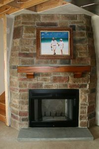 Brick wall mounted fireplace with painting above