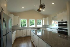 Large white kitchen with dark granite countertop