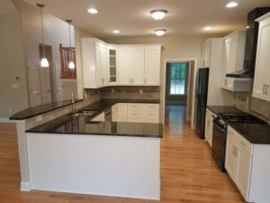 White kitchen cabinets with dark granite countertop