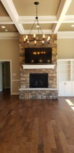 Brick wall mounted fireplace with TV above