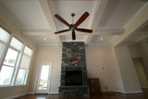Dark brown ceiling fan next to the fireplace