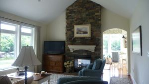 Brick wall mounted fireplace with painting above inside of the living room