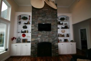 Brick wall mounted fireplace with TV above surrounded by white built in cabinets