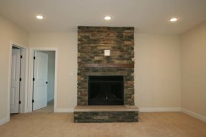 Brick wall mounted fireplace inside of an empty room