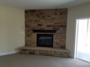 Brick wall mounted fireplace in the corner of the room