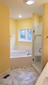 Yellow bathroom with the bathtub in the middle