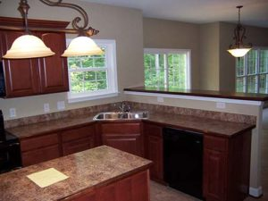 Wooden kitchen cabinets with marble countertop next to the forest