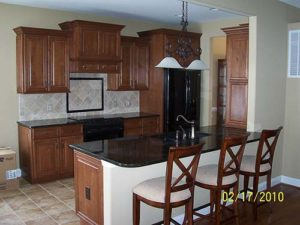 Wooden kitchen bar with granite countertop and three stools
