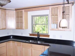 Wooden cabinets with granite countertop inside of kitchen