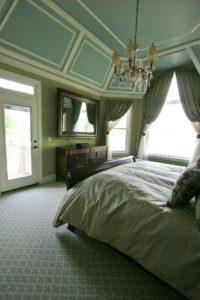 Bedroom bed below the chandelier