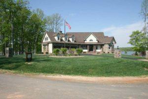 House near lake with an american flag
