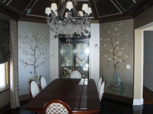 Dining table with chandelier next to the painting on the wall